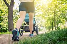 Walking woman with baby stroller enjoyin