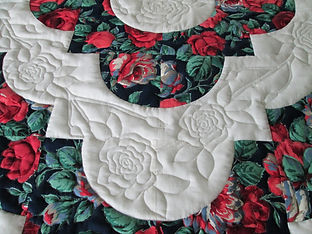 Close up of free motion quilted roses on white background