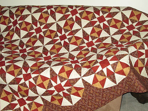 Focus on Circles Faux Border Quilt, paper pieced in rich shades of brown, red, gold, and cream