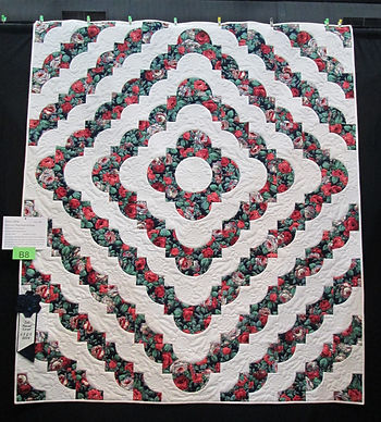 Ring Around the Roses Quilt, blue ribbon winner, red roses and green leaves on black background, alternating with white, using Drunkard's Path block