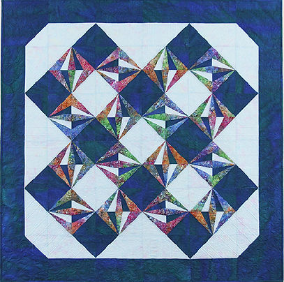 Peek-a-Boo Blocks paper pieced, faux border quilt, dark and light blue background with bright multi-colored fabric shapes as accents on blocks, 36 blocks, no borders