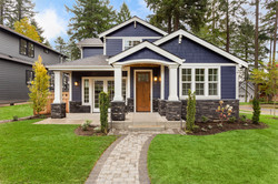 Beautiful exterior of newly built luxury home.jpg Yard with green grass and walkway lead to ornately
