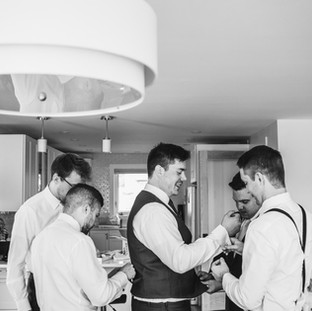 Groom getting ready with friends. Black and white groom