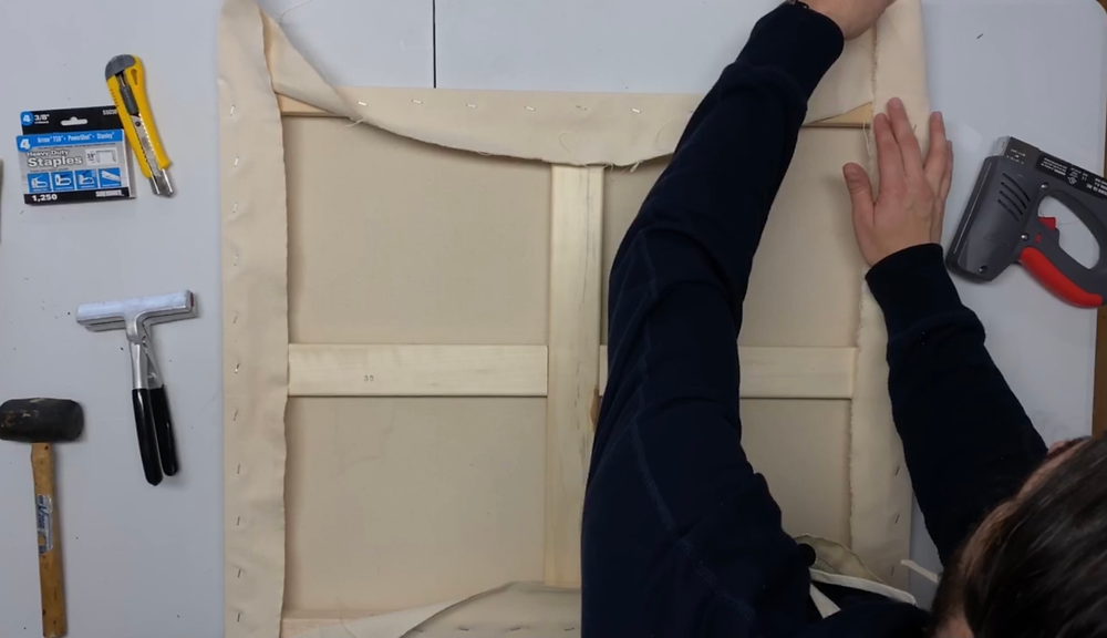 Hold the canvas down and make a nice clean 45 degree fold