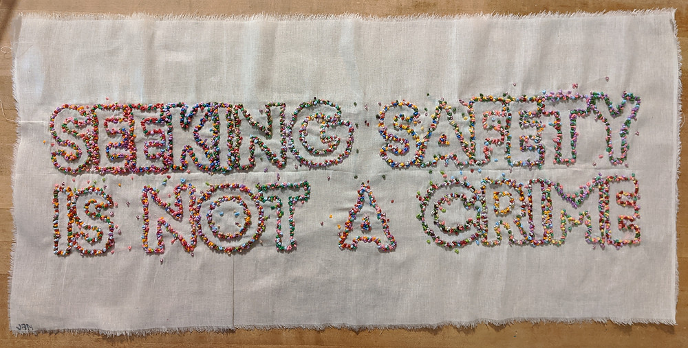 Seeking safety is not a crime in multiple colors created with french knots on ivory fabric