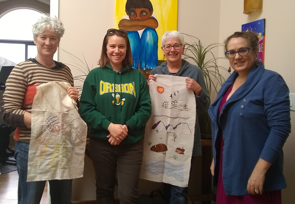 4 female adults - two of which are holding embroidered panels of fabric