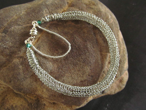 Handmade bracelet of knitted silver wire and green Swarovski crystals