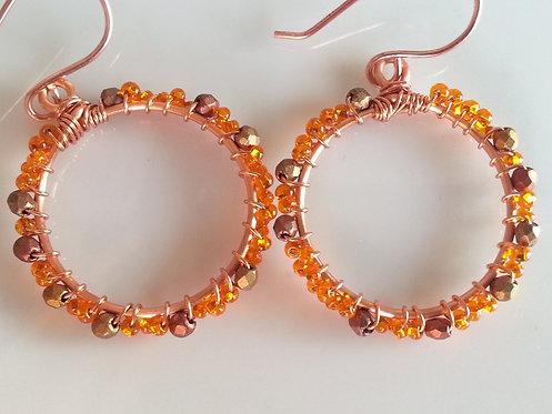 Handmade earrings one-inch hoops of copper wrapped in copper & orange glass