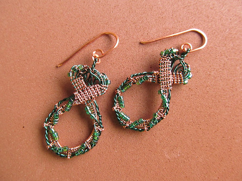 Handmade earrings of wire woven copper and evergreen with green glass
