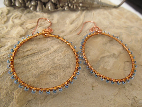 Handmade wire wrapped copper hoop earrings with sky blue glass