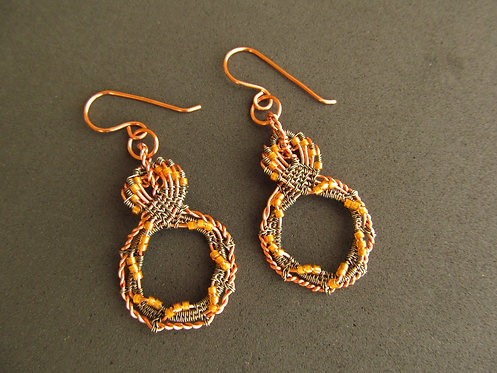 Handmade earrings of wire woven hematite and copper with butterscotch glass