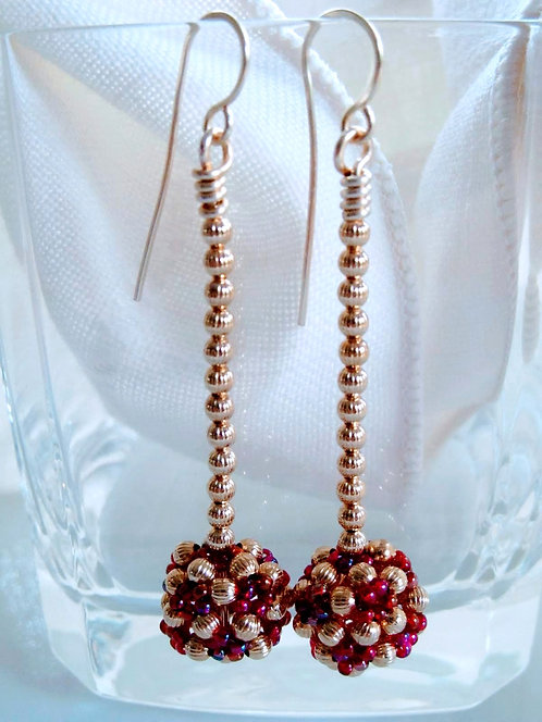 Handmade earrings of hand beaded purple-ish glass and brass beads on gold