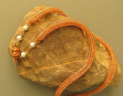Necklace of knitted copper with glass pearls