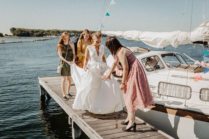 Sommerhochzeit am Veerse Meer in Holland. Natürliche Hochzeitsreportage. getting ready. Heiraten in Holland. Boho Hochzeit in Holland. Hochzeit am Veerse Meer. Gäste erwarten die Braut. Veerse Meer. Braut auf dem Segelboot. Braut auf dem Steg.Heiraten in Holland. Heiraten am Meer.