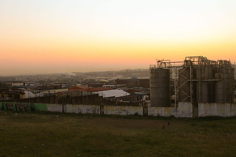 Landscape picture of South Durban, South Africa, highlighting the industrial region. The sky is a faded yellow-orange with smog appearing on the land.