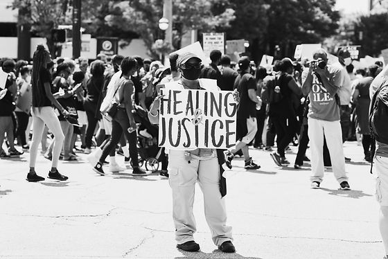 """Black and white image of a brown skinned protestor holding a sign that says """"Healing and Justice."""""""