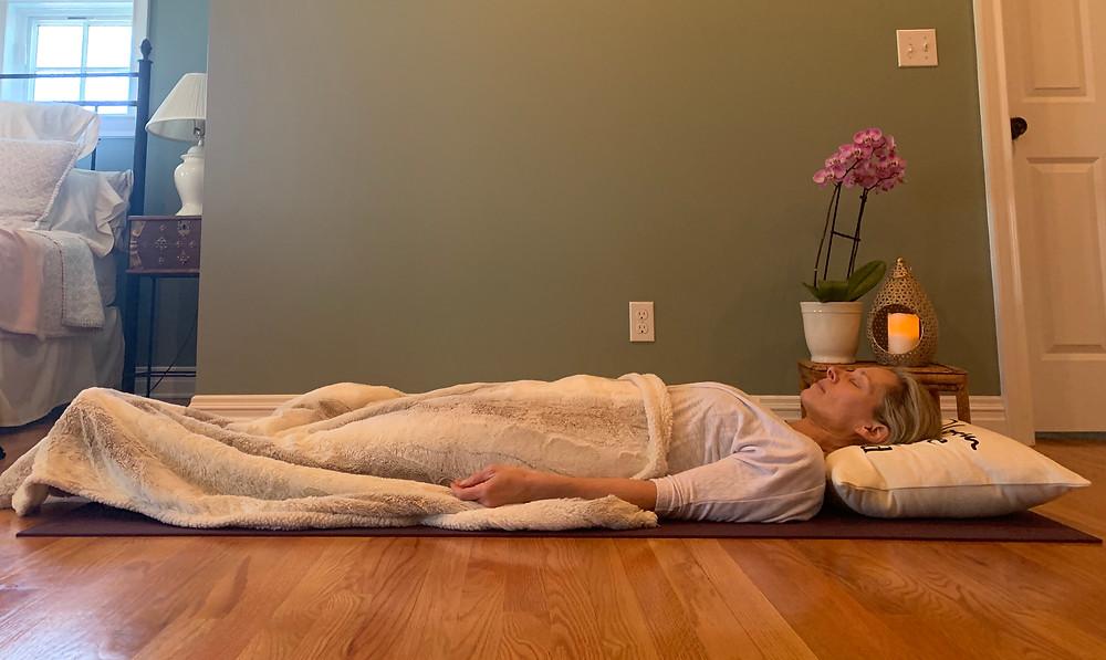 Me, lying in savsana, covered in a cozy blanket.