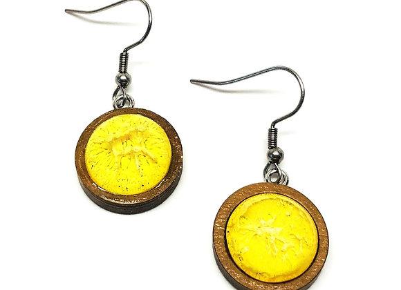 "Tresino Lumina 0.75"" longyellow resin earrings on a brown wood base front"