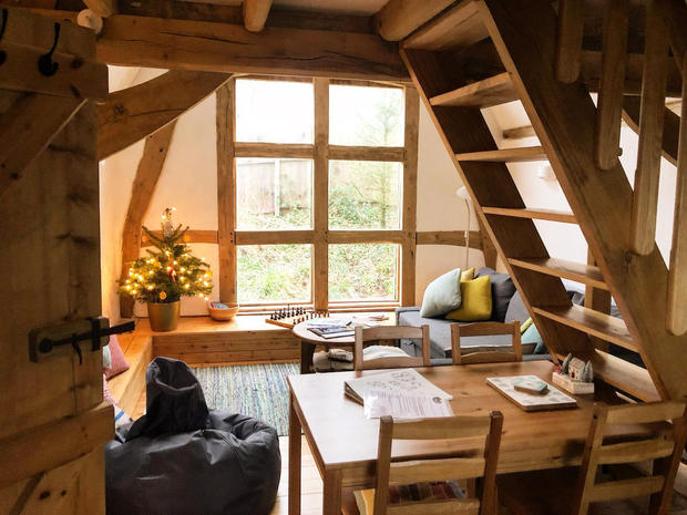 Cosy Oak Framed building interiors - small oak framed barn convention done in 2017. Cruck Framed structure with thatch roof, sheep's wool insulation, woodwool & lime internal plaster finish.