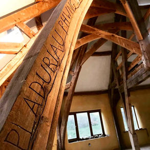 Carved oak beams that form part of a conical roof gable end extension.