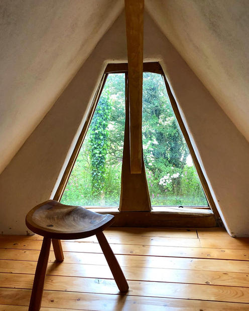 Beautiful small windows looking out from a small mezzanine floor on a oak framed cabin we made. The roof is a lime plaster on wood wool boards with wood fiber insulation batts. This systems allows for a healthy living space whilst also being an environmentally conscious design and build.