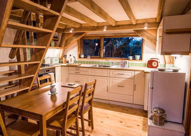 The interior of a small oak framed cabin with crog loft.