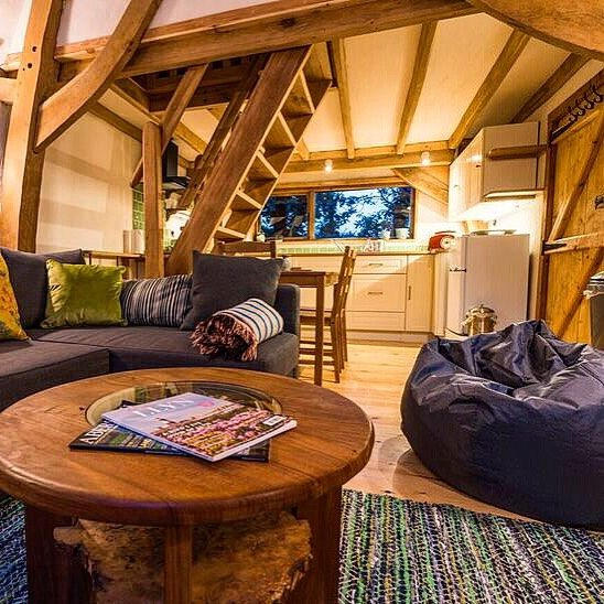 Cosy cruck framed barn oak interior - thatched roofed storage barn converted into a small quirky living area with a crogloft.