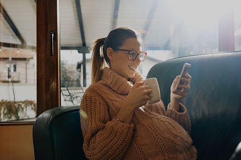 Cheerful Pregnant woman sitting on couch looking at cell phone with coffee in hand