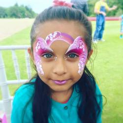 A pink rainbow fairy face paint.