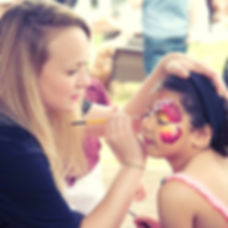 A girl being painted as a beautiful pink and yellow butterfly designed by Emily's Entertainment