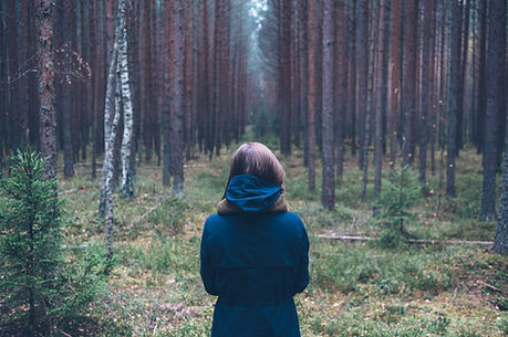 Woman alone in the woods looking off into the distance. Feeling lonely.