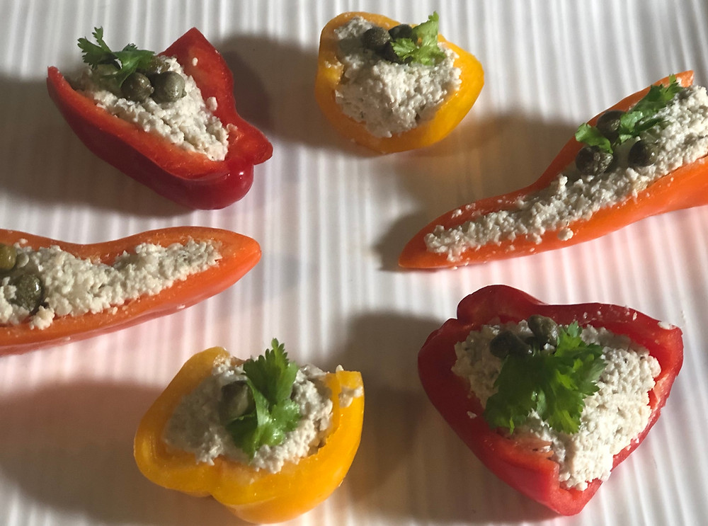 Mini-Bell-Peppers cut in half and filled with Vegan Tuna. Garnished with cappers and cilantro leaves.