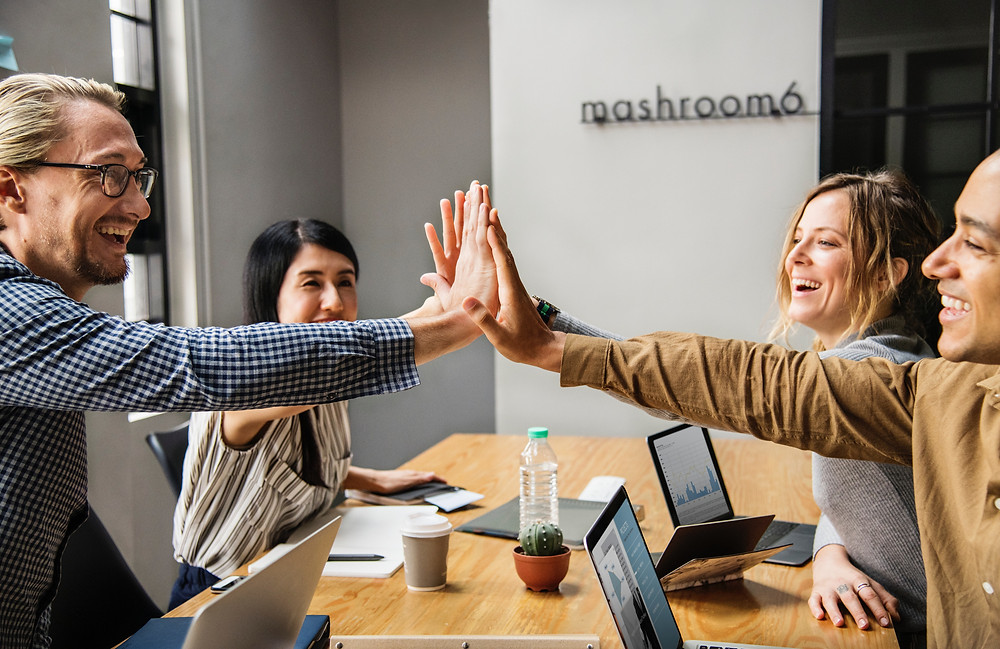 Diverse team of employees high fiving and co-working over a communal desk.