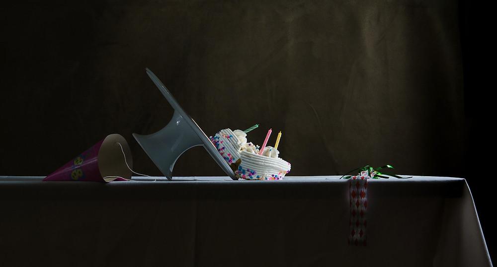 Cake has been broken in half as it falls off a platter.