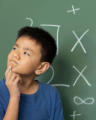 schoolboy-doing-math-on-green-chalkboard