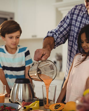 father-preparing-smoothie-with-his-kids-