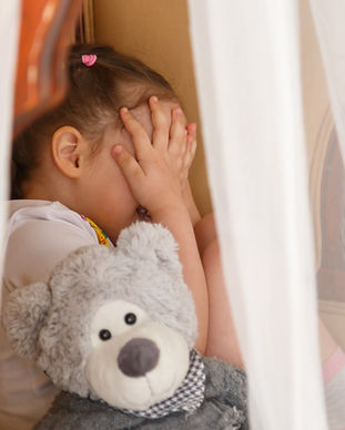 little-kid-hiding-behind-teddy-bear-PUKS