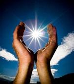 Foto de duas mãos juntas, com o sol no meio