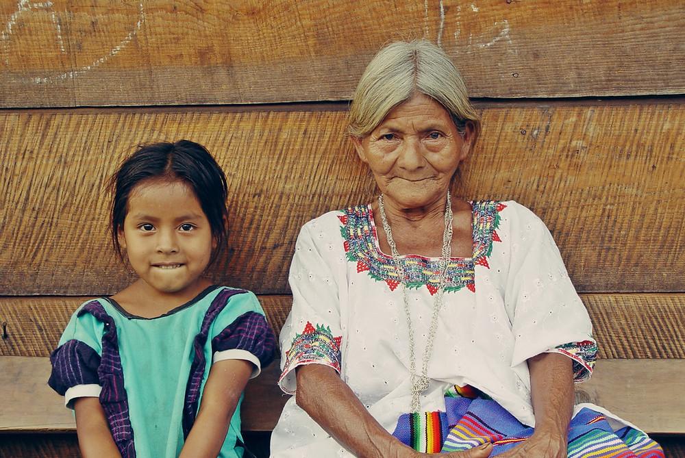 Avó e neta sentadas no chão felizes