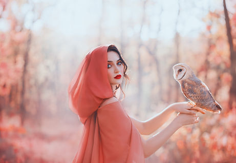 mystical pagan woman covered head peach scarf hood silk cape in autumn magic forest, holds