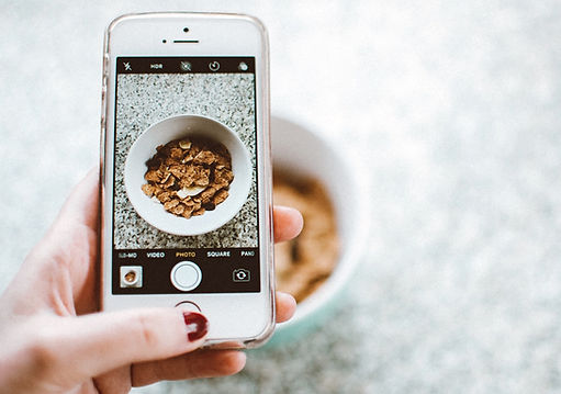 Taking a photo with an iPhone of a bowl of cereal.