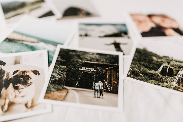 A collection of printed photos laying on a bed.