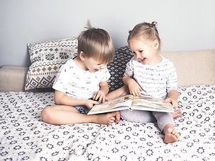 Two young children reading a book together and laughing.