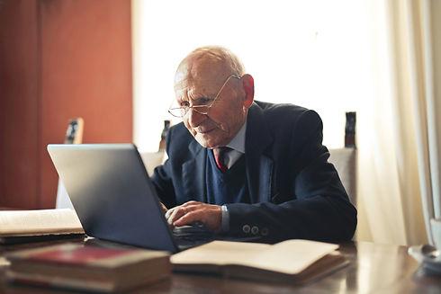 Adretter alter Mann sitzt am Laptop.jpg