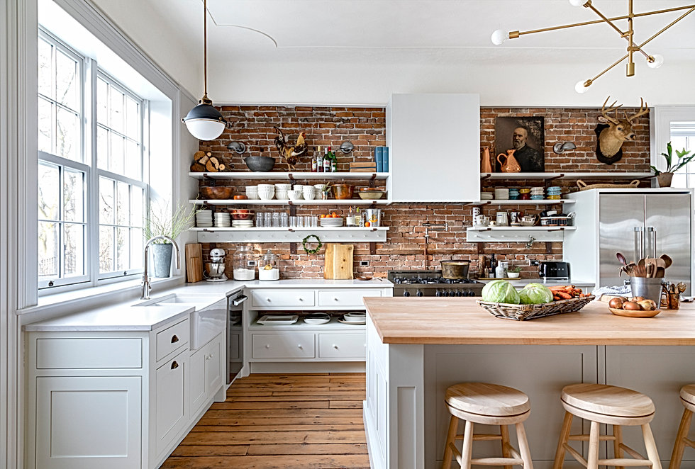 white kitchen with brick wall