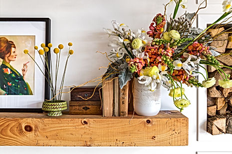 A vase filled with flowers on a shelf.