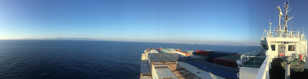 containership as seen from aboard it. relatively calm water and horizon.