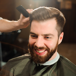 Master cuts hair and beard of men in the