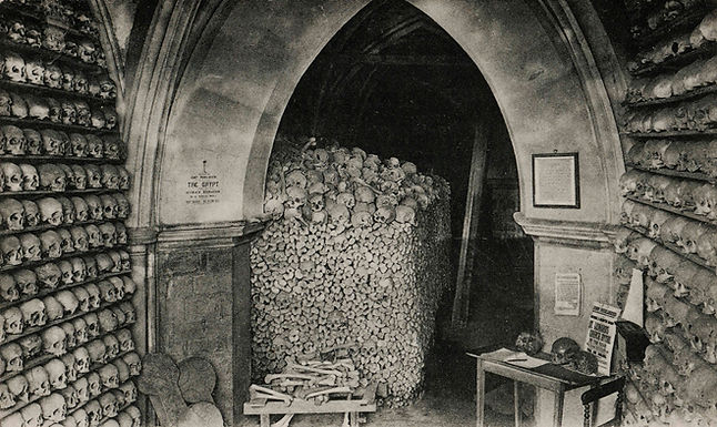 Bones in the ambulatory of St. Leonard's Church in Hythe, depicted c.1910. The skulls were arranged on shelves in the mid-19th century and are displayed like this to this day. Author's collection.  Details: Postcard. Pub c.1910; J. Davis, Queen Victoria Street, E.C. (Canterbury East?).