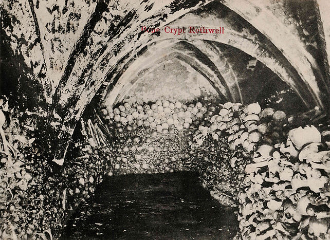 The charnel at Holy Trinity Church, Rothwell. This photograph, taken c.1900, depicts the crypt's arrangement before it was reorganised for conservation purposes in 1911. Author's collection.  Details: Postcard. Pub c.1905; H. Evans, Market Place, Kettering.